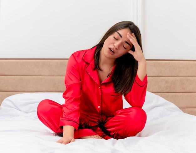 疲れているように見える仕事の日後に疲労感を感じてベッドに座っている赤いパジャマの若い美しい女性は、明るい背景の寝室のインテリアで眠りたいです