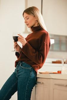 キッチンに立って、1本の指で彼女の手でグラスワインに触れる赤いセーターの若い美しい女性
