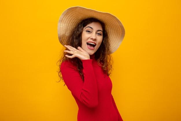 Молодая красивая женщина в красной водолазке в летней шляпе счастлива и весело улыбается, широко стоя на оранжевом