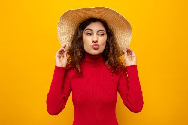 여름 모자를 쓴 빨간 터틀넥을 입은 젊은 아름다운 여성이 주황색 벽 위에 서서 키스하는 것처럼 입술을 옆으로 바라보고 있습니다.