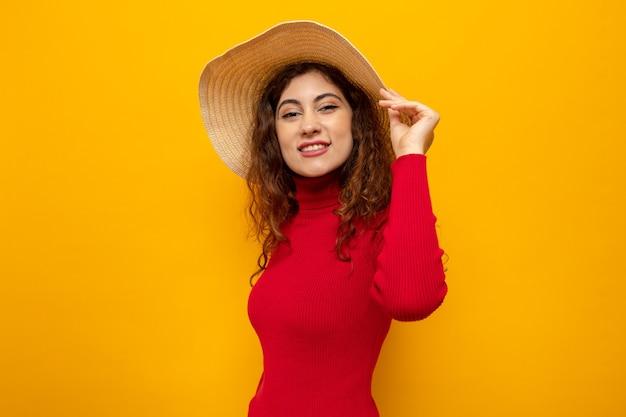Молодая красивая женщина в красной водолазке в летней шляпе выглядит счастливой и веселой, широко улыбаясь