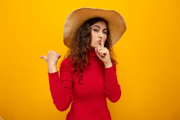 Молодая красивая женщина в красной водолазке в летней шляпе смотрит, делая жест молчания с пальцем на губах