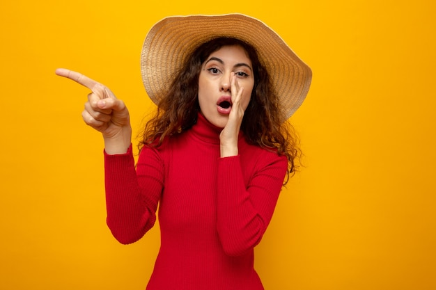 Молодая красивая женщина в красной водолазке в летней шляпе выглядит удивленной, рассказывая секрет рукой над ртом, указывая пальцем в сторону