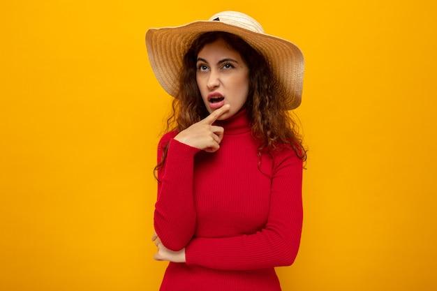 オレンジ色の上に立っている物思いにふける表情で見上げる夏の帽子の赤いタートルネックの若い美しい女性