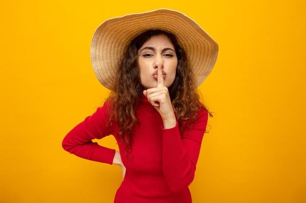オレンジ色の上に立っている唇に指で沈黙のジェスチャーを作る夏の帽子の赤いタートルネックの若い美しい女性