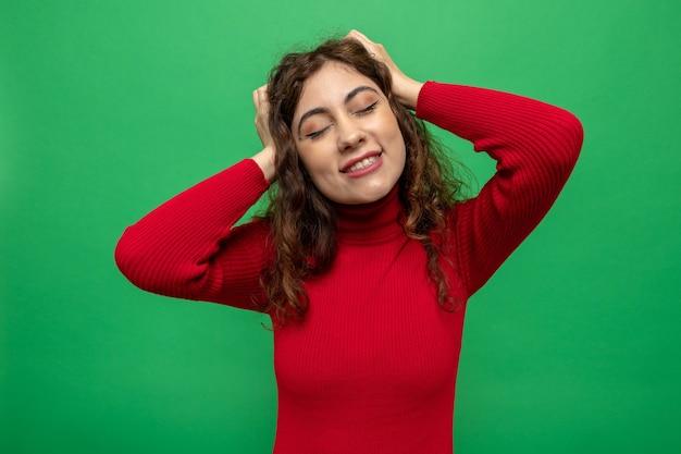 彼女の頭に触れる赤いタートルネックの若い美しい女性は、緑の壁の上に立って目を閉じて幸せで前向きな夢を見る