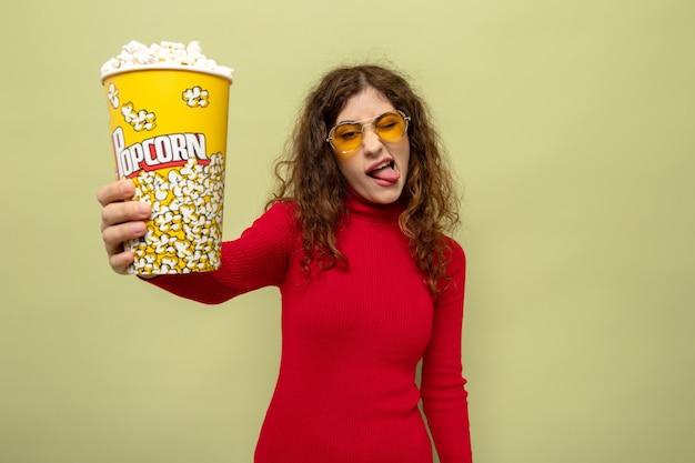 Молодая красивая женщина в красной водолазке в желтых очках держит ведро попкорна, счастливая и радостная, высунув язык, стоя на зеленом