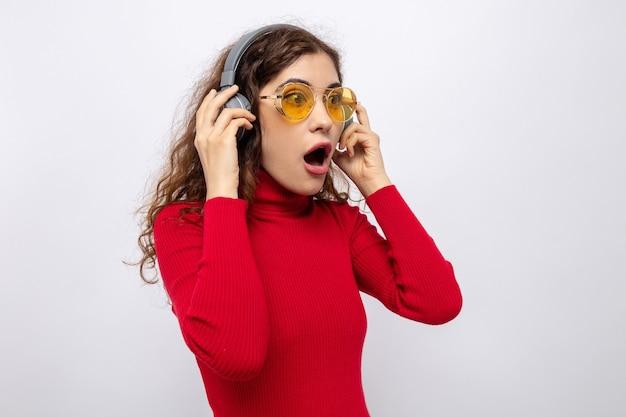 Молодая красивая женщина в красной водолазке с наушниками в желтых очках смотрит в сторону изумленно и удивленно