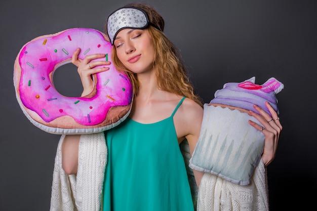 面白いクッションとパジャマの若い美しい女性