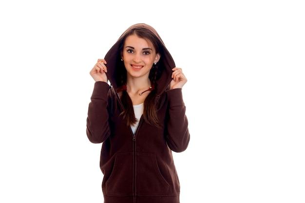 후드보고와 격리 된 흰 벽 웃 고 스포츠 옷에서 젊은 아름 다운 여자