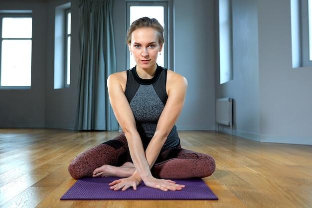 체육관에서 창 앞 바닥에 앉아있는 동안 스트레칭 하 고 운동복에 젊은 아름 다운 여자