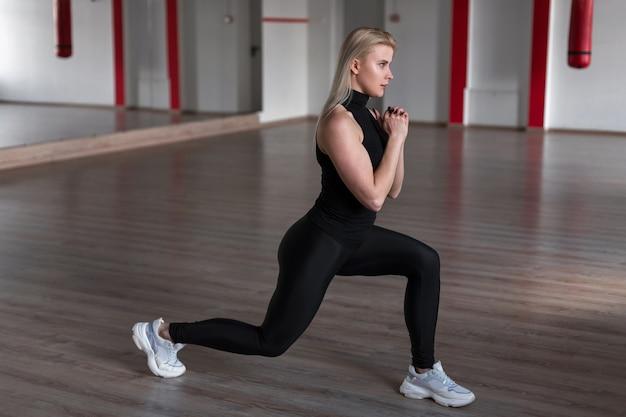 Молодая красивая женщина в спортивной черной стильной униформе на тренировке в тренажерном зале