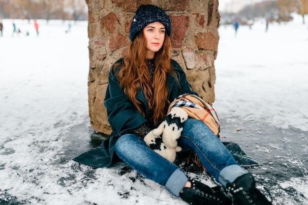Молодая красивая женщина в стильной одежде с длинными каштановыми волосами, сидя под мостом на льду на замерзшем озере в холодный морозный зимний день