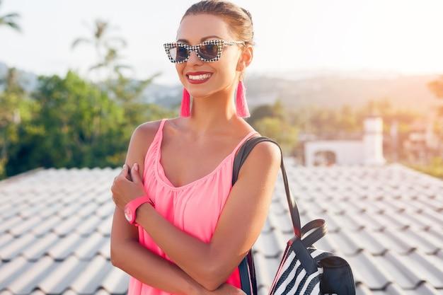 Молодая красивая женщина в стильных солнцезащитных очках смотрит в камеру, модные аксессуары, летние тенденции в моде, уличный стиль, улыбается, счастлива, серьги