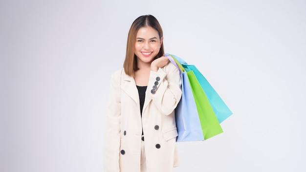 Молодая красивая женщина в костюме, держащая красочные хозяйственные сумки на белом фоне студии