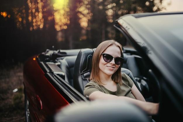 笑顔のサングラスでコンバーチブル夏の若い美しい女性
