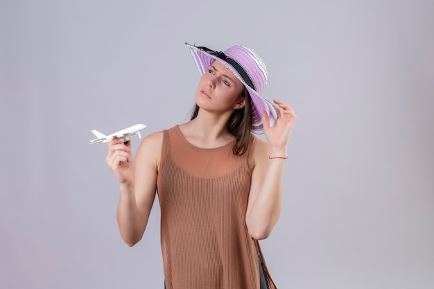 Молодая красивая женщина в летней шляпе держит игрушечный самолетик, глядя в сторону, думая с задумчивым выражением лица, стоя на белом фоне