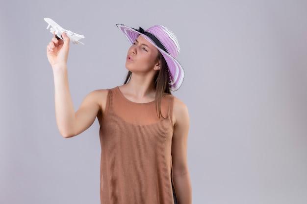 Молодая красивая женщина в летней шляпе держит игрушечный самолет, глядя игривая и счастливая над белой стеной