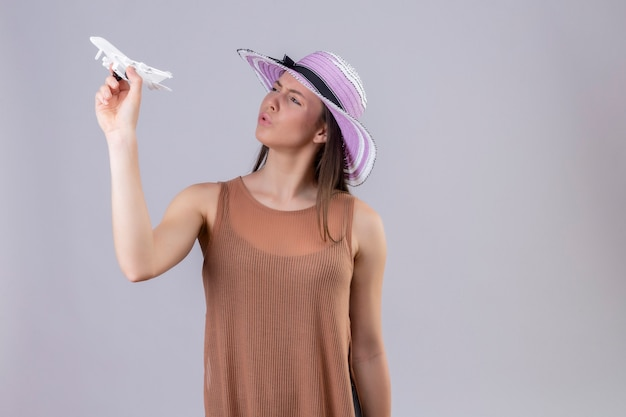 Молодая красивая женщина в летней шляпе держит игрушечный самолетик, выглядя игривым и счастливым, стоя на белом фоне