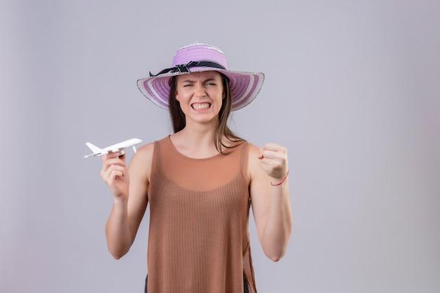 Молодая красивая женщина в летней шляпе держит игрушечный самолет, поднимая кулак с сердитым выражением над белой стеной