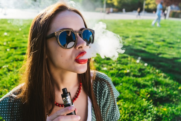선글라스를 쓴 젊고 아름다운 여성이 밝은 녹색 잔디가 있는 잔디밭에 앉아 담배를 피우고 있습니다. 맑은 날