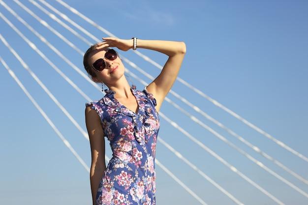 青い空に太陽を見ているサングラスの若い美しい女性