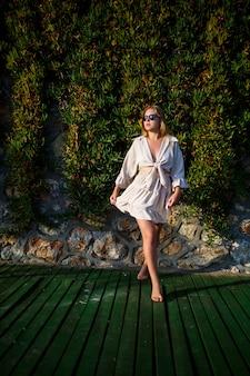サングラスをかけた若い美しい女性は明るい太陽の下を歩きます、彼女はベージュの短いスカートとトップにいます