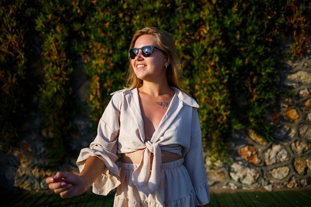 선글라스를 쓴 젊은 미녀는 밝은 태양 아래서 걷고, 베이지색 짧은 치마와 상의를 입고 있다