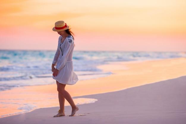 Молодая красивая женщина на фоне заката океана