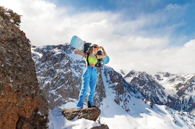 그녀의 어깨에 스노보드와 수영복에 젊은 아름 다운 여자는 산 경사면을 본다