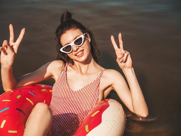 水着と海に浮かぶサングラスの若い美しい女性