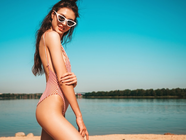 水着とサングラスのビーチでポーズの若い美しい女性