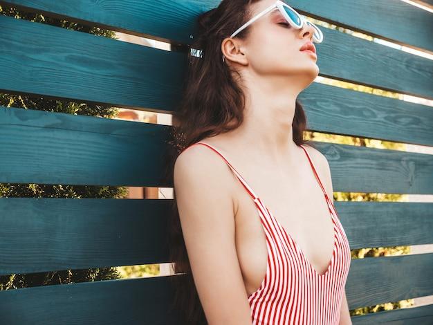 Молодая красивая женщина в купальниках и солнцезащитные очки, позирует на улице