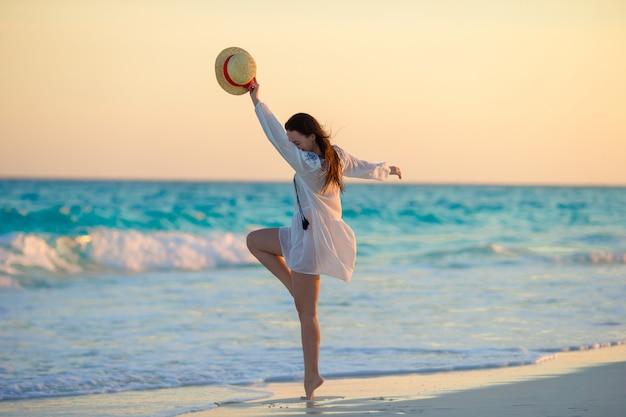 Молодая красивая женщина на пляже с заката свет