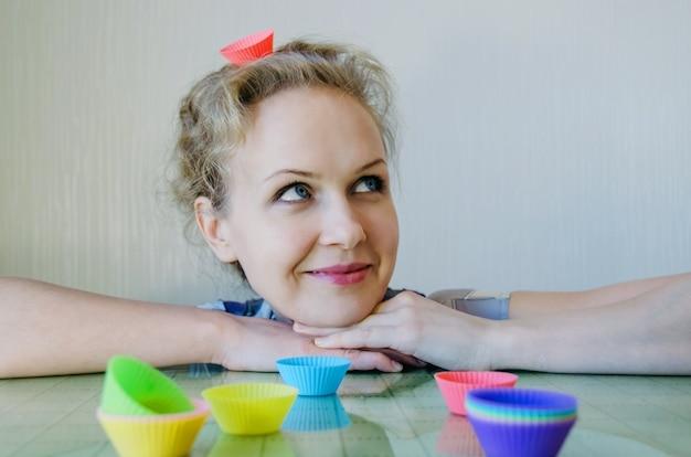 Молодая красивая женщина на кухне печет кексы