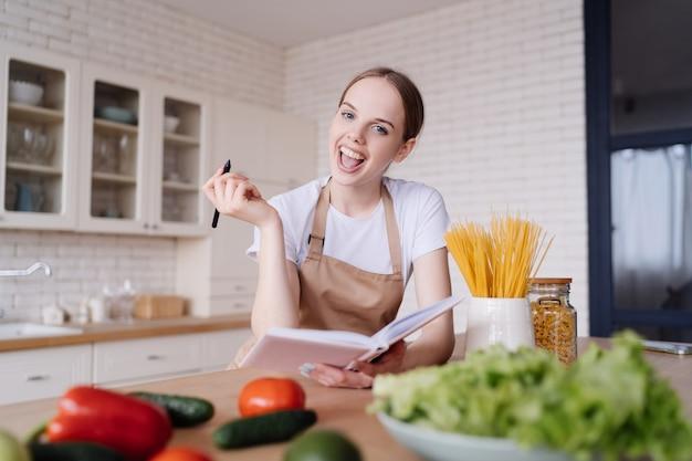 앞치마에 부엌에서 젊은 아름다운 여자가 신선한 야채 옆에 그녀가 좋아하는 요리법을 기록