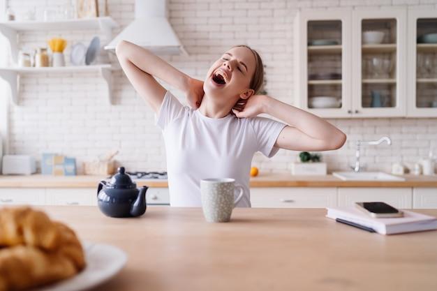 朝、キッチンでお茶を飲みながらストレッチする若い美しい女性 Premium写真