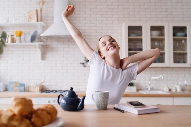 朝、キッチンでお茶を飲みながらストレッチする若い美しい女性