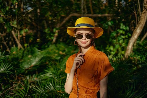 帽子の熱帯ジャングルの中で若い美しい女性は、自然主義者、公園を散歩します