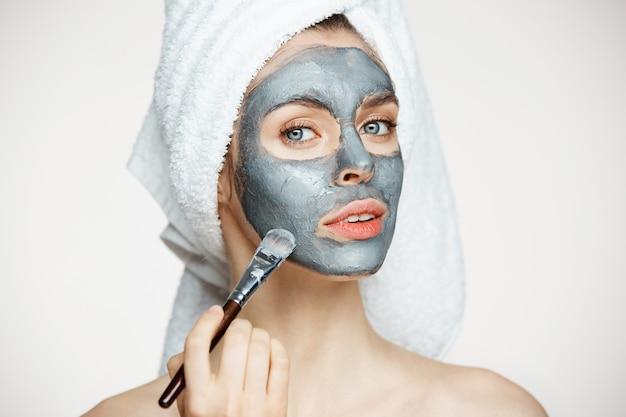 Молодая красивая женщина в полотенце на голову, охватывающих лицо с улыбкой маску. косметология и спа.