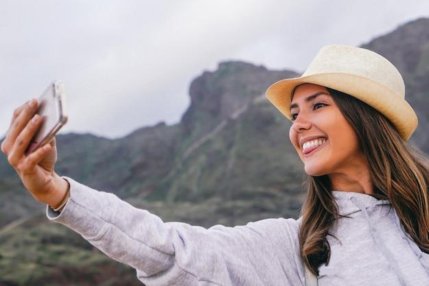 그녀의 모바일 스마트 폰 카메라와 함께 selfie을 복용 휴가에서 젊은 아름 다운 여자
