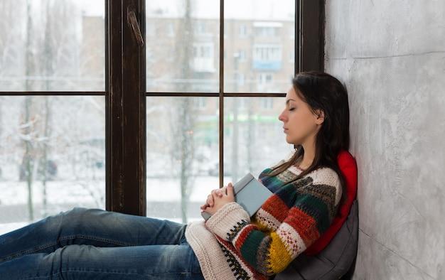本を読んでいる間、暖かいニットのセーターを着た若い美しい女性が枕で窓辺で眠りに落ちる