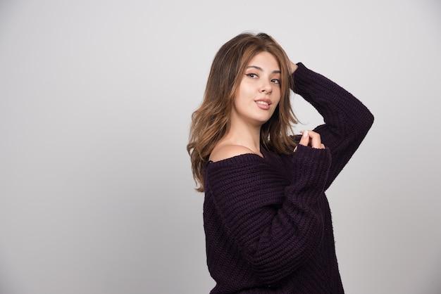 Молодая красивая женщина в теплом вязаном свитере стоя и позирует.
