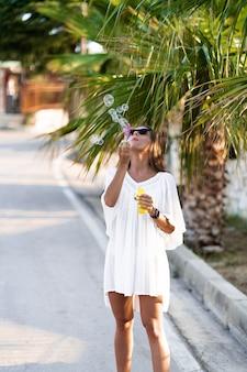Молодая красивая женщина в белом платье и солнцезащитные очки, дует мыльные пузыри на дороге с ладонями. концепция радости, легкости и свободы во время отдыха. девушка наслаждается отдыхом.