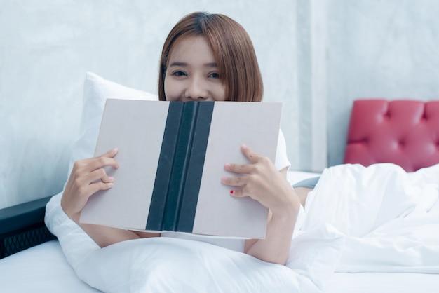 Молодая красивая женщина в белом белье, читая книгу в постели