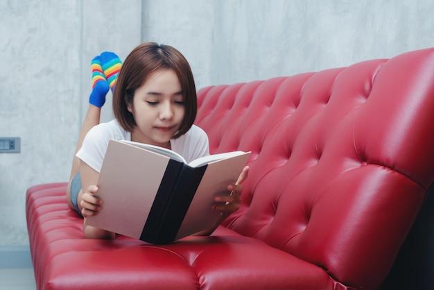 Молодая красивая женщина в белом нижнем белье, читая книгу в постели