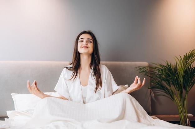 흰색 실크 잠옷을 입은 젊은 미녀가 침실에서 요가를 하고 있습니다. 침대에 연꽃 위치에 여성 모델입니다. 여성 모델과 함께 침실에서 아침이나 저녁.