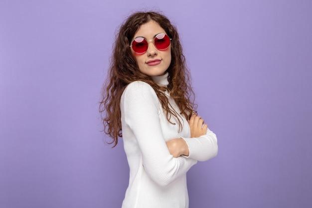 紫色の壁に自信を持って表情と腕を組んで横に立っている赤い眼鏡をかけている白いタートルネックの若い美しい女性