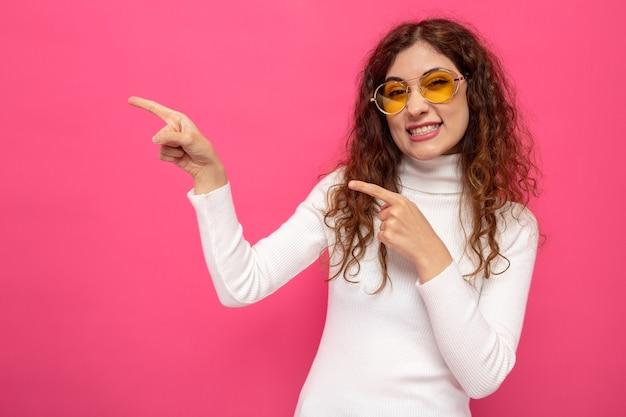 ピンクの上に立っている側に人差し指で幸せで陽気なポインティング黄色のメガネを身に着けている白いタートルネックの若い美しい女性