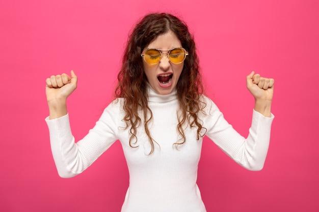 노란 안경을 쓴 흰색 터틀넥을 입은 젊고 아름다운 여성이 분홍색 벽 위에 주먹을 들고 공격적인 표정으로 소리를 지르고 있다